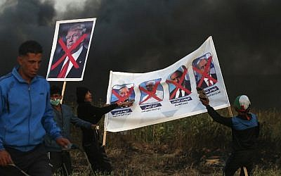 Palestinian protesters hold posters bearing images of Israeli politicians and the US president during clashes with Israeli security forces following a protest along the border with Israel, east of Gaza City on April 5, 2018 ( AFP PHOTO / MOHAMMED ABED)