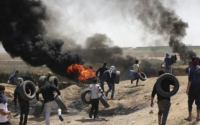 Palestinian men collect tires and burn them at the Israel-Gaza border during a protest east of Gaza City, on April 6, 2018. (AFP/Mahmud Hams)
