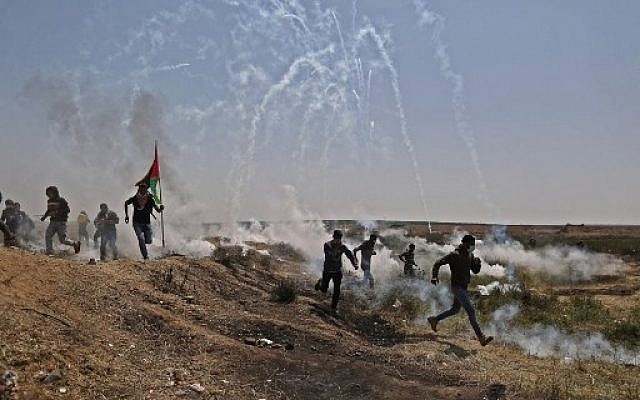 Palestinian men run for cover from tears gas canisters at the Israel-Gaza border during a protest, east of Gaza City in the Gaza strip, on April 6, 2018. (AFP PHOTO / MAHMUD HAMS)