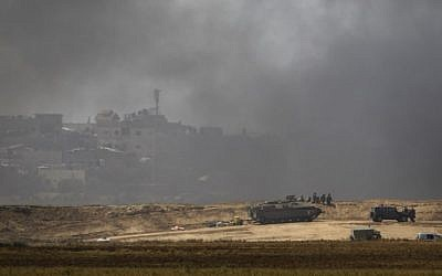 Israeli forces are deployed near Kibbutz Nir Oz at the Gaza-Israel border amid smoke from tires burned by Palestinians near Khan Younis, in the southern part of the Gaza Strip on April 6, 2018. (AFP Photo/Menahem Kahana)