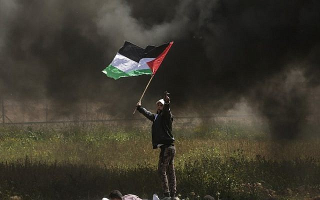 A Palestinian protestor waves his national flag during clashes with Israeli security forces on the Gaza-Israel border, east of Gaza City on April 6, 2018. (AFP PHOTO / MAHMUD HAMS)