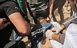 Demonstrators assist injured Palestinian journalist Yasser Murtaja during clashes with Israeli security forces, following a protest near the border with Israel, east of Khan Yunis in the southern Gaza Strip, on April 6, 2018. Murtaja later died of his wounds. (AFP/Said Khatib)