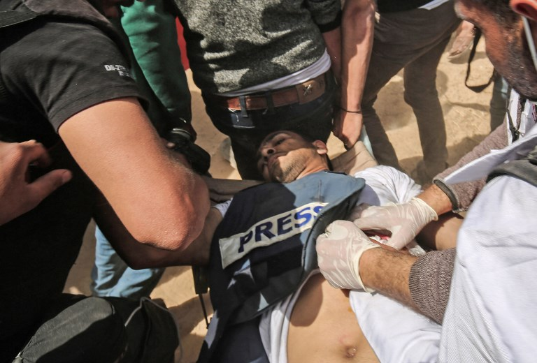 Demonstrators assist an injured Palestinian journalist Yasser Murtaga during clashes with Israeli security forces following a protest near the border with Israel east of Khan Yunis in the southern Gaza Strip