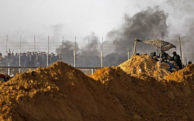 Illustrative: Israeli security forces face protesters near Kibbutz Kerem Shalom on the border with the southern Gaza Strip on April 6, 2018 (AFP PHOTO / MENAHEM KAHANA)