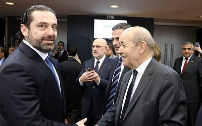 Lebanese Prime Minister Saad Hariri (L) shakes hands with French Foreign Affairs Minister Jean-Yves Le Drian as they attend a conference in Paris on April 6, 2018. (AFP/Pool/Ludovic Marin)