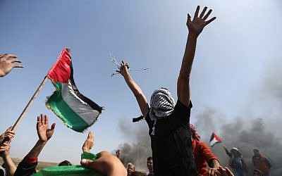 Palestinian demonstrators wave their national flag and shouts slogans against Israeli security forces during a protest on the Israel-Gaza border in the northern Gaza Strip on April 6, 2018. (AFP/Mohammed Abed)