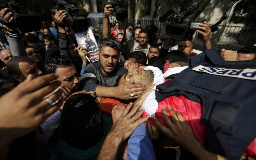 Mourners and journalists carry the body of Palestinian journalist Yasser Murtaja, during his funeral in Gaza City on April 7, 2018. (AFP Photo/Mahmud Hams)