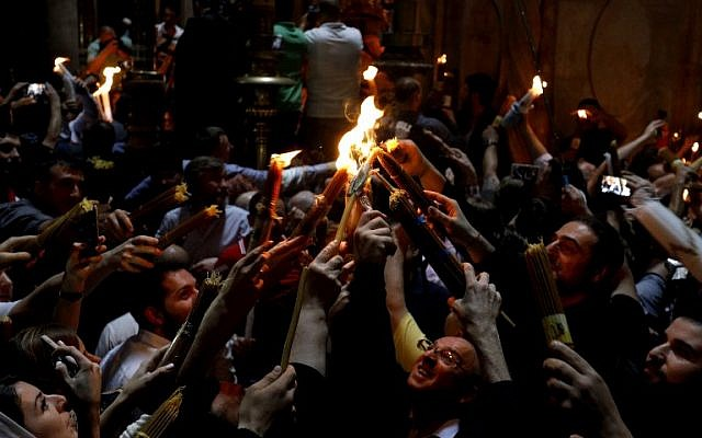 Christian Orthodox worshippers holds up candles lit from the 'Holy Fire' as they gather in the Church of the Holy Sepulchre in Jerusalem's Old City on April 7 ,2018 during the Orthodox Easter. (AFP PHOTO / GALI TIBBON