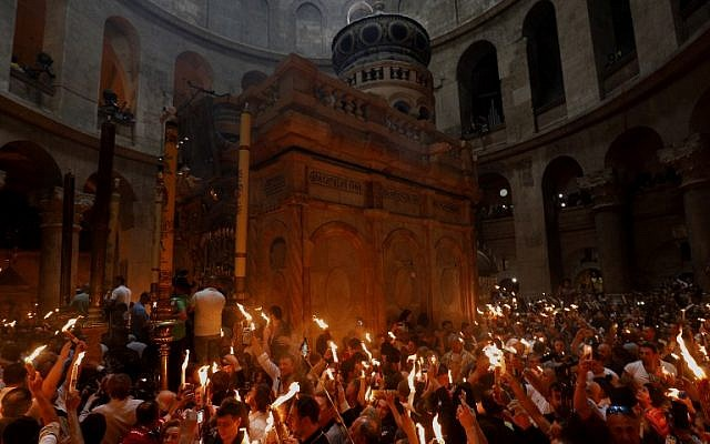 Christian Orthodox worshippers hold up candles lit from the 'Holy Fire' as they gather in the Church of the Holy Sepulchre in Jerusalem's Old City on April 7, 2018 during the Orthodox Easter. (AFP PHOTO / GALI TIBBON)