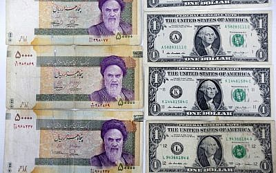 A close up shot shows Iran's various Rial banknotes, bearing a portrait of Iran's late founder of Islamic Republic Ayatollah Ruhollah Khomeini, next to United States one-Dollar bills bearing a portrait of first US President, George Washington at a currency exchange office in a shopping center in the capital Tehran on April 10, 2018. (AFP PHOTO / ATTA KENARE)