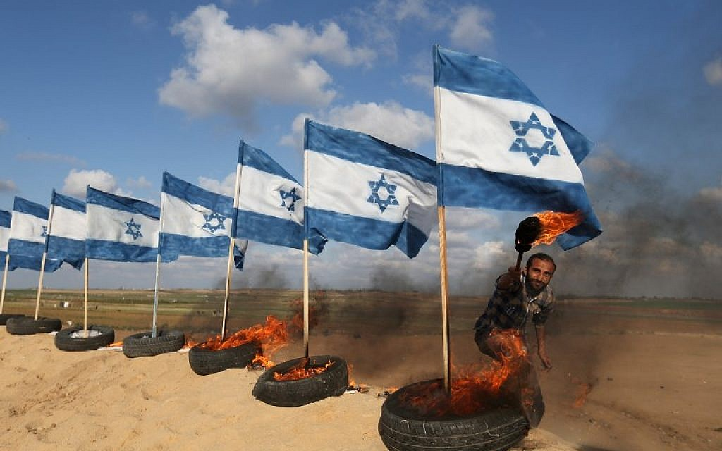 A Palestinian protestor prepares to set fire on Israeli flags on April 10, 2018 at the site of protests on the Israel-Gaza border east of Jabalia in the northern Gaza Strip. (AFP PHOTO / Mohammed ABED)