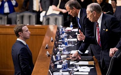 Facebook CEO Mark Zuckerberg (L) speaks with Senator John Thune (C), R-SD, and Senator Chuck Grassley (R), R-IA following a joint hearing of the Senate Commerce, Science and Transportation Committee and Senate Judiciary Committee on Capitol Hill April 10, 2018 in Washington, DC. (AFP PHOTO / Brendan Smialowski)