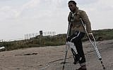 Tamer Abu Daqqa, a Palestinian who says he was shot by an Israeli sniper along the Gaza border during a protest, walks with crutches near the Gaza-Israel border near Khan Yunis in the southern Gaza Strip on April 11, 2018. (AFP PHOTO/SAID KHATIB)
