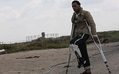 Tamer Abu Daqqa, a Palestinian who says he was shot by an Israeli sniper along the Gaza border during a protest, walks with crutches near the Gaza-Israel border near Khan Yunis in the southern Gaza Strip on April 11, 2018. (AFP PHOTO/SAID KHATIB)
