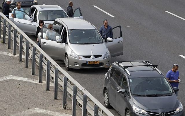 Drivers stop and stand in silence on a highway in the Israeli city of Tel Aviv on April 12, 2017 as sirens wailed across Israel for two minutes marking the annual day of remembrance for the six million Jewish victims of the Nazi genocide. (AFP PHOTO / JACK GUEZ)