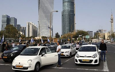 Drivers stop and stand in silence on a street in the Israeli city of Tel Aviv on April 12, 2017 as sirens wailed across Israel for two minutes marking the annual day of remembrance for the six million Jewish victims of the Nazi genocide. (AFP PHOTO / JACK GUEZ)