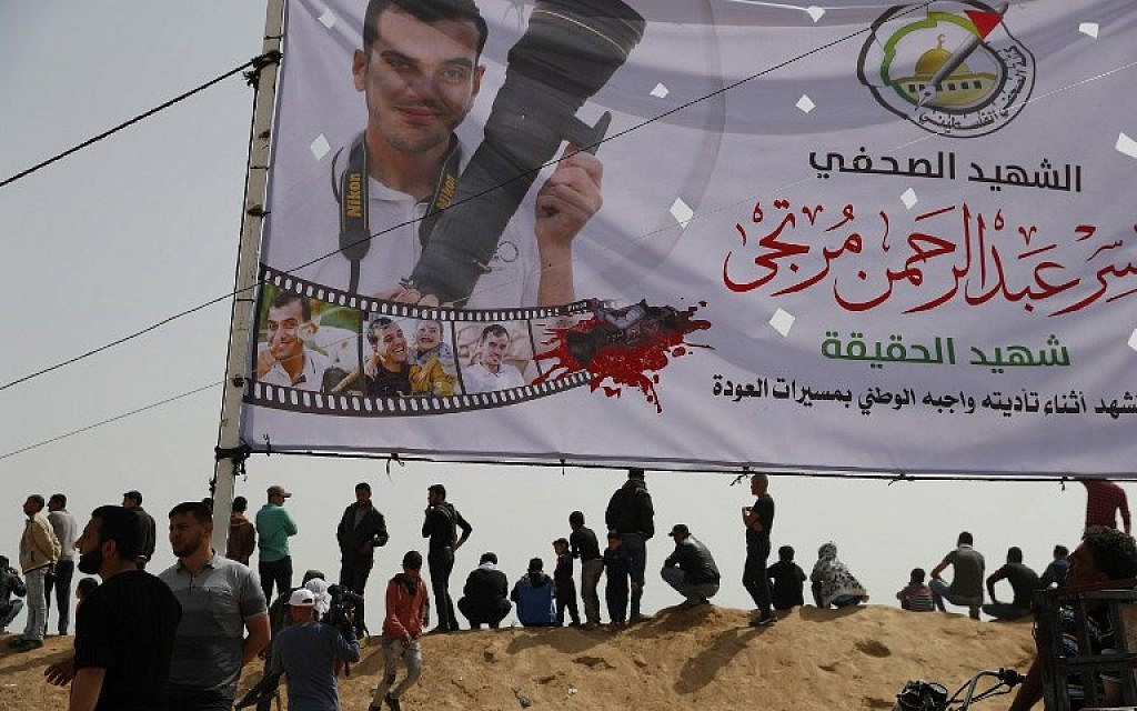 Palestinians gather near a banner in memory of Yasser Murtaja, a Gaza reporter killed last week by Israeli fire, during a protest at the border fence with Israel, east of Khan Yunis in the southern Gaza city, on April 13, 2018. (AFP PHOTO / Thomas COEX)