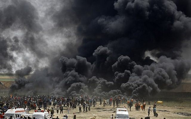 Palestinians burn tires at the border fence with Israel, east of Jabalia in the central Gaza city, during a protest on April 13, 2018. (AFP PHOTO / MOHAMMED ABED)