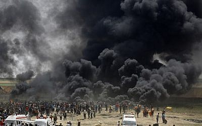 Illustrative: Palestinians burn tires at the border fence with Israel, east of Jabalia in the central Gaza city, during a protest on April 13, 2018.(AFP PHOTO / MOHAMMED ABED)