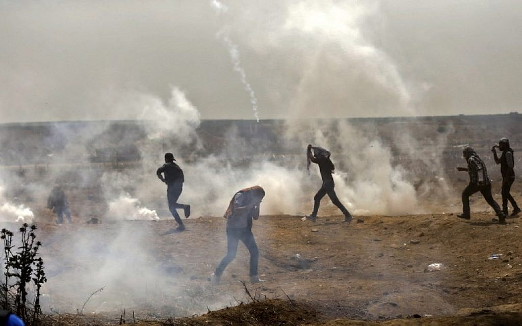 Palestinians take cover from tear gas smoke during clashes with Israeli security forces near the border fence with Israel, east of Gaza City in the central Gaza Strip on April 13, 2018.(AFP PHOTO / MAHMUD HAMS)
