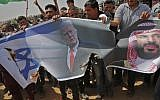 Palestinians prepare to set fire to an Israeli flag and portraits of US President Donald Trump and Saudi Crown Prince Mohammed bin Salman during a protest at the border fence between Israel and the Gaza Strip, April 13, 2018. (AFP/Thomas Coex)