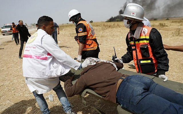 Illustrative: Palestinians paramedics evacuating an injured protester near the border fence with Israel, east of Khan Yunis, in the southern Gaza city, on April 13, 2018. (AFP PHOTO / Thomas COEX)