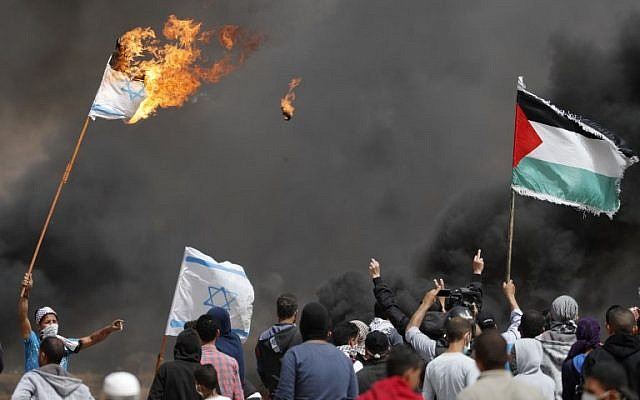Palestinian protesters burn Israeli flags near the border fence with Israel, east of Khan Yunis in the southern Gaza city, on April 13, 2018. (AFP/Thomas Coex)