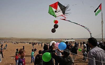 Palestinians fly a kite as they gather at the border fence with Israel, east of Jabalia in the central Gaza city, during a protest on April 13, 2018. (AFP/Mohammed Abed)