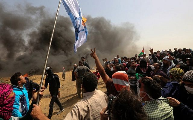 Palestinian protesters burn an Israeli flag during clashes with Israeli forces near the border with Israel, east of Gaza city in the central Gaza strip, on April 13, 2018. (/ AFP PHOTO / MAHMUD HAMS )