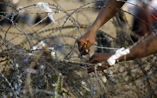 A Palestinian man tries to cut through a section of barbed wire at the border fence with Israel, east of Jabalia in the central Gaza city, during a protest on April 13, 2018 (AFP PHOTO / MOHAMMED ABED)