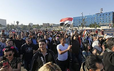 Syrians wave the national flag and wave portraits of President Bashar al-Assad as they gather at the Umayyad Square in Damascus on April 14, 2018, to condemn the strikes carried out by the United States, Britain and France against the Syrian regime. (AFP PHOTO / LOUAI BESHARA)