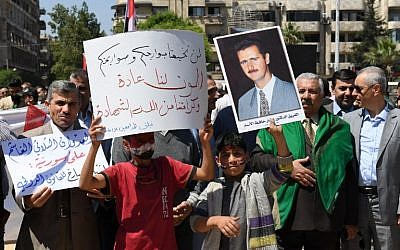 Syrians wave the national flag and wave portraits of President Bashar al-Assad as they gather in Aleppo's Saadallah al-Jabiri square on April 14, 2018, to condemn the strikes carried out by the United States, Britain and France against the Syrian regime. (AFP PHOTO / George OURFALIAN)