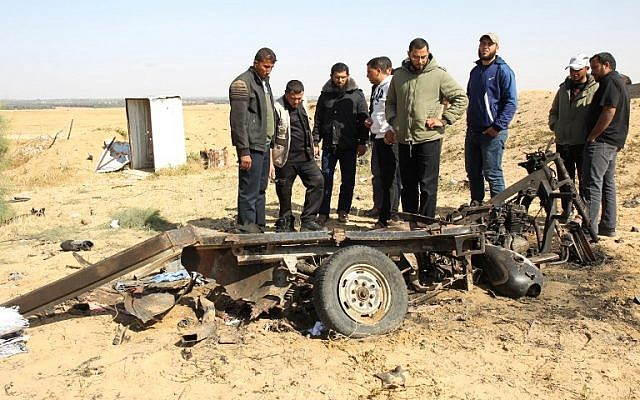 Illustrative: Palestinian men look at the debris of a tuk tuk vehicle at the site of an explosion east of Rafah in the southern Gaza Strip, on April 14, 2018. Four members of Islamic Jihad died in the blast (AFP PHOTO / SAID KHATIB)