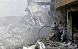Syrian soldiers inspect the wreckage of a building described as part of the Scientific Studies and Research Center (SSRC) compound in the Barzeh district, north of Damascus, during a press tour organised by the Syrian information ministry, on April 14, 2018. (AFP / LOUAI BESHARA)
