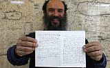 Meron Eren, co-founder and owner of the Kedem auction house, holds a letter by German anti-Semitic composer Richard Wagner in Jerusalem on April 16, 2018. (Menahem Kahana/AFP)