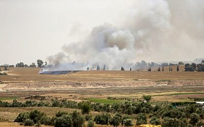 Illustrative: Smoke and flames rise from fields near the Kibbutz Be'eri on the Israeli side of the border with the Gaza Strip east of Gaza City, after Palestinians flew a kite laden with a Molotov cocktail over the border before cutting the string leaving the burning material to fall in Israeli territory on April 17, 2018. (AFP/Mahmud Hams)