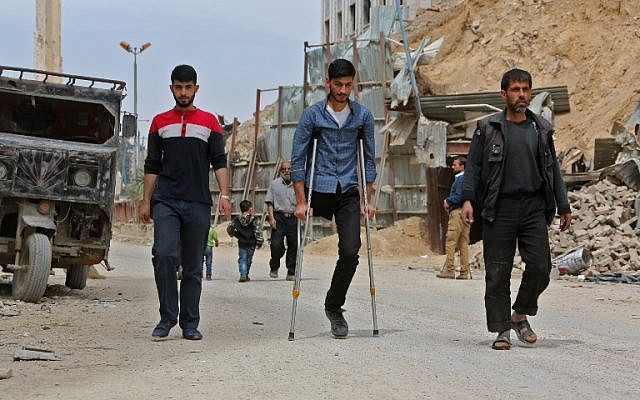 Civilians walk in the former rebel Syrian town of Douma on the outskirts of Damascus on April 17, 2018 after the Syrian army declared that all anti-regime forces have left Eastern Ghouta, following a blistering two month offensive on the rebel enclave. ( AFP PHOTO / STRINGER)
