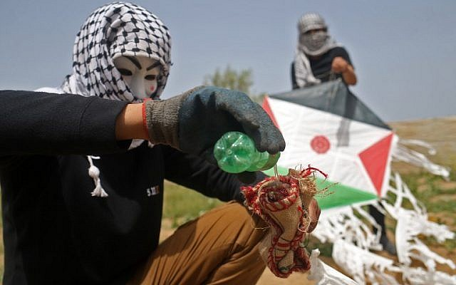 Palestinians on the eastern outskirts of Gaza City prepare a firebomb to attach to a kite and fly over the border fence with Israel, on April 20, 2018. (AFP Photo/Mohammed Abed)