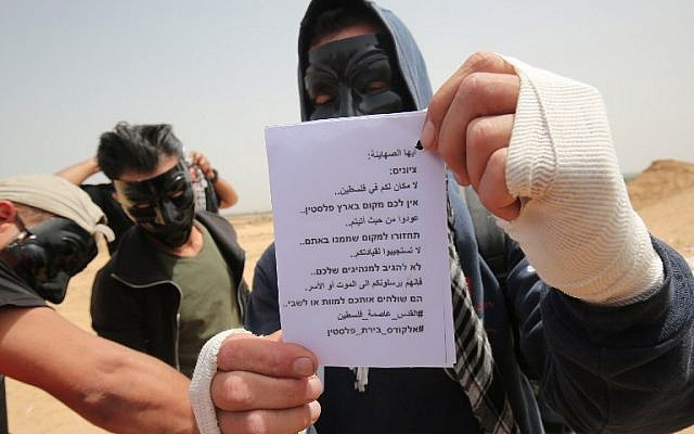 "Palestinians display leaflets that will be attached to kites carrying firebombs before being flown over the border fence with Israel, Rafah, southern Gaza Strip, April 20, 2018. The message on the leaflet reads in Hebrew and in Arabic, 'Zionists: There is no place for you in Palestine. Go back to where you came from. Do not obey your leaders. They send you to death or captivity. #Jerusalem capital of Palestine"" (AFP Photo/Said Khatib)"
