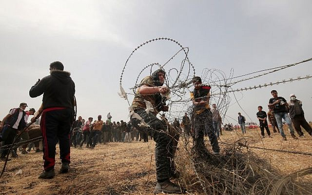 Illustrative. Palestinians pull barbed wire from the border fence with Israel during weekly Friday clashes, in Rafah in southern Gaza Strip, on April 20, 2018. (AFP Photo/Said Khatib)