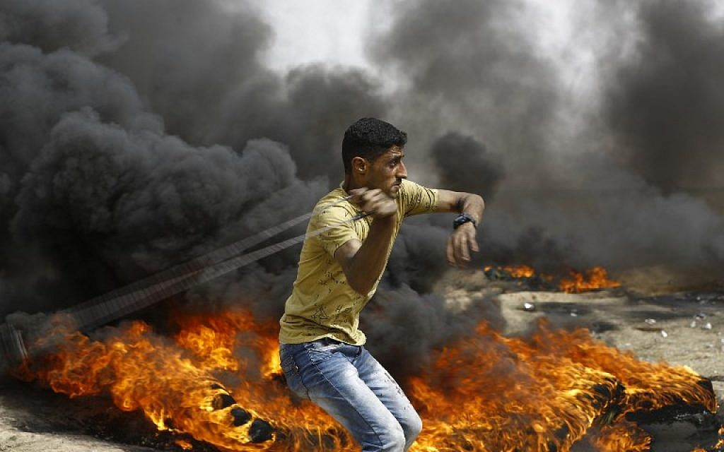 A Palestinian slings a shot by burning tires during clashes with Israeli forces across the border, east of Gaza City, in the southern Gaza Strip, on April 20, 2018. (MOHAMMED ABED / AFP)