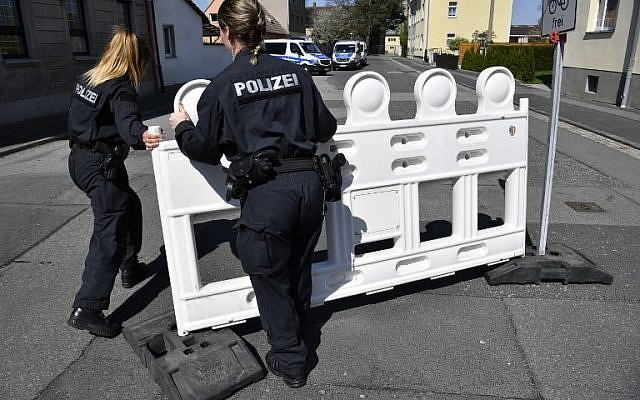"""German policewomen fence off an area on April 20, 2018, as part of the security measures ahead of the """"Schild und Schwert"""" (Shield and Sword, or SS) neo-nazi festival, in the small eastern German town of Ostritz. ( AFP PHOTO/John MACDOUGALL)"""