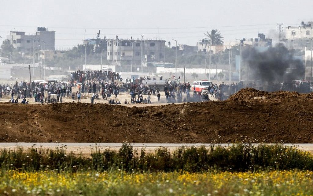 A picture taken from the southern Israeli kibbutz of Nahal Oz across the border with the Gaza Strip shows Palestinians rioting along the border fence on April 20, 2018. (AFP Photo/Ahmad Gharabli)
