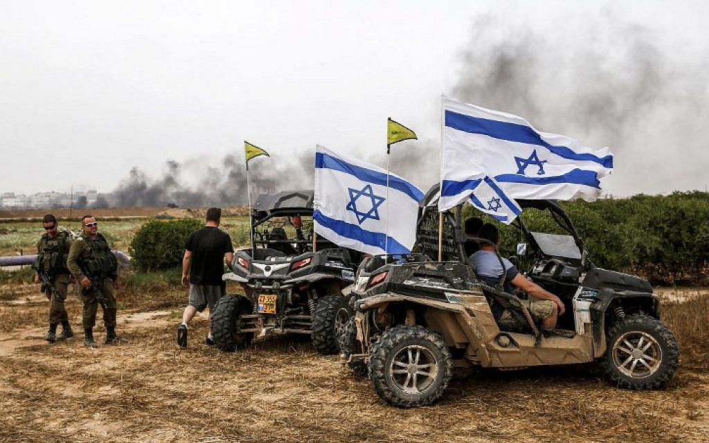 Israelis sit in parked dune buggies flying Israeli flags near IDF soldiers in the southern kibbutz of Nahal Oz on April 20, 2018, across from the border with Gaza as Palestinians take part in violent protests along the fence. (AFP Photo/Ahmad Gharabli)
