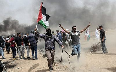 Palestinian protesters pull a metal cable as they try to take down a section of barbed wire during clashes with Israeli forces on April 20, 2018, east of Khan Yunis, in the southern Gaza Strip (AFP PHOTO / SAID KHATIB)