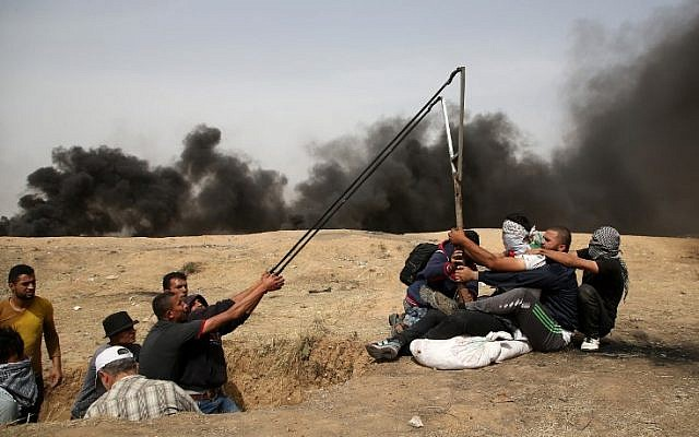 A group of Palestinians man a large sling to hurl stones during clashes with Israeli forces across the border, east of Gaza City, on April 20, 2018. (AFP Photo/Mohammed Abed)