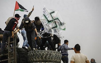 Palestinians hold a kite adorned with a swastika that is carrying a pipe bomb during clashes with Israeli forces across the border with Israel east of Gaza City, on April 20, 2018. (AFP Photo/Mohammed Abed)
