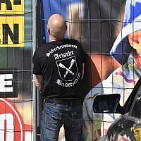Private security personel with 'Aryan Brotherhood' on his T-shirt opens the gate at the venue of the 'Schild und Schwert' (Shield and Sword) neo-Nazi festival, in the small eastern German town of Ostritz on April 20, 2018.( AFP PHOTO / John MACDOUGALL)