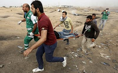 Palestinian medics evacuate a wounded protester during clashes with Israeli forces on April 20, 2018, east of Gaza City (AFP PHOTO / MOHAMMED ABED)