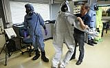 A man shows a suit (R) used by OPCW experts in the case of Russian double agent Sergei Skripal's poisoning in Britain, as a man (L) wears an air permeable charcoal impregnated suit, combined with a respirator (or gas mask), rubber boots and three layers of gloves during a simulation at the OPCW (The Organisation for the Prohibition of Chemical Weapons) headquarters in The Hague, The Netherlands, on April 20, 2017. (AFP PHOTO / JOHN THYS)